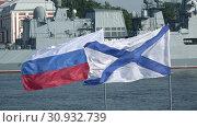 Купить «Российский и Андреевский флаги развеваются на фоне военного корабля. День ВМФ в Санкт-Петербурге», видеоролик № 30932739, снято 28 июля 2018 г. (c) Виктор Карасев / Фотобанк Лори