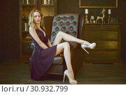 Купить «Sexy young woman in a purple dress sits in a large vintage leather executive chair in an expensive luxury dark interior», фото № 30932799, снято 4 ноября 2017 г. (c) katalinks / Фотобанк Лори
