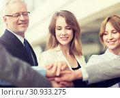 Купить «business people putting hands on top in office», фото № 30933275, снято 3 июля 2016 г. (c) Syda Productions / Фотобанк Лори