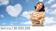 Купить «woman hugging herself over heart shaped cloud», фото № 30933335, снято 6 марта 2019 г. (c) Syda Productions / Фотобанк Лори