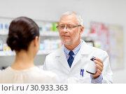 Купить «apothecary and woman with drug at pharmacy», фото № 30933363, снято 27 июня 2015 г. (c) Syda Productions / Фотобанк Лори