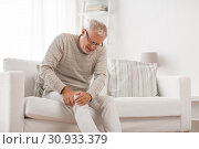 senior man suffering from knee ache at home. Стоковое фото, фотограф Syda Productions / Фотобанк Лори