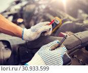 Купить «auto mechanic man with multimeter testing battery», фото № 30933599, снято 1 июля 2016 г. (c) Syda Productions / Фотобанк Лори