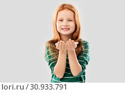 smiling red haired girl holding something on palms. Стоковое фото, фотограф Syda Productions / Фотобанк Лори