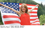 Купить «Patriotic holiday. Happy emotional woman with American flag on green forest background during summer day outdoors. USA celebrate 4th of July.», видеоролик № 30933947, снято 9 июня 2019 г. (c) Ольга Балынская / Фотобанк Лори