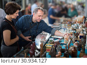Купить «Cheerful tourists study the range of flea market», фото № 30934127, снято 19 июля 2019 г. (c) Яков Филимонов / Фотобанк Лори