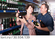 Купить «Portrait of an elderly couple buying a beer at the grocery store», фото № 30934139, снято 20 июля 2019 г. (c) Яков Филимонов / Фотобанк Лори