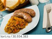 Купить «Sausages with stewed cabbage», фото № 30934383, снято 18 июля 2019 г. (c) Яков Филимонов / Фотобанк Лори