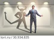 Devil hiding in the businessman - alter ego concept. Стоковое фото, фотограф Elnur / Фотобанк Лори