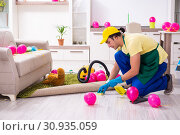 Купить «Young male contractor doing housework after party», фото № 30935059, снято 14 марта 2019 г. (c) Elnur / Фотобанк Лори