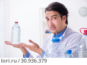 Купить «Young male chemist experimenting in lab», фото № 30936379, снято 5 марта 2019 г. (c) Elnur / Фотобанк Лори