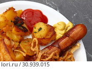Купить «Close up portion of one big grilled sausage with homemade roasted potato, fried onion rings, ketchup and mustard on white plate over grey table, elevated top view, directly above», фото № 30939015, снято 29 марта 2017 г. (c) easy Fotostock / Фотобанк Лори