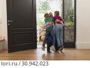 Купить «Father embracing his children as he enters the house», фото № 30942023, снято 12 марта 2019 г. (c) Wavebreak Media / Фотобанк Лори
