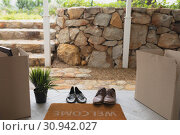 Купить «Footwear, cardboard boxes and plant near welcome doormat», фото № 30942027, снято 12 марта 2019 г. (c) Wavebreak Media / Фотобанк Лори