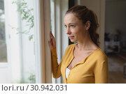 Купить «Woman looking outside through window in a comfortable home», фото № 30942031, снято 12 марта 2019 г. (c) Wavebreak Media / Фотобанк Лори