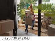 Купить «Mother and children with cardboard boxes walking towards home», фото № 30942043, снято 12 марта 2019 г. (c) Wavebreak Media / Фотобанк Лори