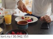 Купить «Man pouring honey on pancake at dining table», фото № 30942151, снято 12 марта 2019 г. (c) Wavebreak Media / Фотобанк Лори