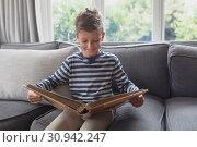 Купить «Boy looking at photo album in living room», фото № 30942247, снято 12 марта 2019 г. (c) Wavebreak Media / Фотобанк Лори