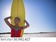 Купить «Beautiful woman in swimwear carrying the surfboard on her head at beach in the sunshine», фото № 30942427, снято 15 марта 2019 г. (c) Wavebreak Media / Фотобанк Лори