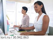 Купить «Female graphic designers working together at desk in a modern office», фото № 30942863, снято 16 марта 2019 г. (c) Wavebreak Media / Фотобанк Лори