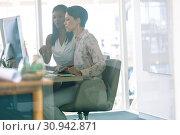 Купить «Female graphic designers discussing on computer at desk in a modern office», фото № 30942871, снято 16 марта 2019 г. (c) Wavebreak Media / Фотобанк Лори