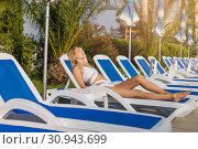 Купить «Young beautiful girl in a bathing suit resting on a lounger on a tropical resort with palm trees», фото № 30943699, снято 18 июля 2017 г. (c) katalinks / Фотобанк Лори