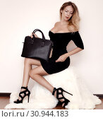 Beautiful luxurious young woman in a black dress sits on a white fur cover in black fashionable sandals and a handbag. Стоковое фото, фотограф katalinks / Фотобанк Лори