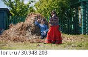 Tatarstan, Laishevo 25-05-2019: Young woman photographing another woman in a haystack. Редакционное видео, видеограф Константин Шишкин / Фотобанк Лори