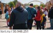 Купить «Tatarstan, Laishevo 25-05-2019: Many people on the street around women in traditional Russian costumes.», видеоролик № 30948251, снято 23 июля 2019 г. (c) Константин Шишкин / Фотобанк Лори