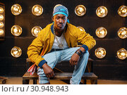 Black rapper in cap sitting on the steps. Стоковое фото, фотограф Tryapitsyn Sergiy / Фотобанк Лори