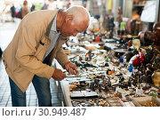 Купить «Senior man chooses rare bell at flea market», фото № 30949487, снято 11 мая 2019 г. (c) Яков Филимонов / Фотобанк Лори