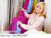Купить «Mature woman customer choosing color curtains», фото № 30949667, снято 17 января 2018 г. (c) Яков Филимонов / Фотобанк Лори