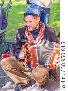 Купить «Russia Samara September 2018: a young man in old Russian clothes plays a musical instrument harp.», фото № 30950815, снято 16 сентября 2018 г. (c) Акиньшин Владимир / Фотобанк Лори