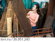 Купить «Female seller offers decorative fence of twigs in store», фото № 30951243, снято 18 сентября 2019 г. (c) Яков Филимонов / Фотобанк Лори