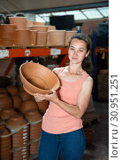 Купить «Young woman customer choosing small clay pot for garden», фото № 30951251, снято 23 июля 2019 г. (c) Яков Филимонов / Фотобанк Лори