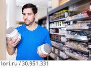Купить «Serious young athletic man buying sport supplements in store», фото № 30951331, снято 28 марта 2018 г. (c) Яков Филимонов / Фотобанк Лори