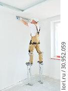 Купить «Painter in stilts with putty knife. Plasterer smoothing ceiling surface at home renewal», фото № 30952059, снято 14 июня 2019 г. (c) Дмитрий Калиновский / Фотобанк Лори