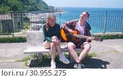 A young couple sitting on a bench on observation deck on a background of the resort town near the sea - playing guitar and sing. Стоковое видео, видеограф Константин Шишкин / Фотобанк Лори