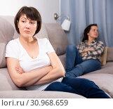 Купить «Mature female sitting at sofa after quarrel quarrel, woman on background», фото № 30968659, снято 19 июня 2019 г. (c) Яков Филимонов / Фотобанк Лори