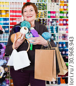 Купить «Woman holding shopping bags and accessories for knitting and embroidery», фото № 30968943, снято 10 мая 2017 г. (c) Яков Филимонов / Фотобанк Лори