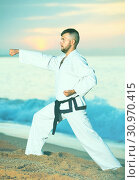 Купить «Man in uniform doing taekwondo exercises at sunset sea shore», фото № 30970415, снято 19 июля 2017 г. (c) Яков Филимонов / Фотобанк Лори