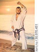 Купить «Glad male doing karate at ocean quay», фото № 30970451, снято 19 июля 2017 г. (c) Яков Филимонов / Фотобанк Лори
