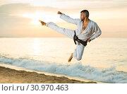 Купить «Man is training kick in jump», фото № 30970463, снято 19 июля 2017 г. (c) Яков Филимонов / Фотобанк Лори