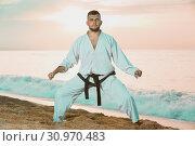 Купить «Guy doing karate poses at sunset sea shore», фото № 30970483, снято 19 июля 2017 г. (c) Яков Филимонов / Фотобанк Лори