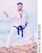 Купить «Guy doing karate poses at sunset sea shore», фото № 30970531, снято 19 июля 2017 г. (c) Яков Филимонов / Фотобанк Лори