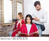 Купить «Positive young man hairdresser cuts hair of young woman with magazine at salon», фото № 30970575, снято 25 апреля 2018 г. (c) Яков Филимонов / Фотобанк Лори