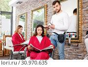 Купить «Positive young man hairdresser cuts hair of young woman with magazine at salon», фото № 30970635, снято 25 апреля 2018 г. (c) Яков Филимонов / Фотобанк Лори