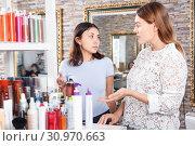 Купить «Young women choosing haircare products at cosmetics showroom», фото № 30970663, снято 25 апреля 2018 г. (c) Яков Филимонов / Фотобанк Лори