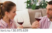 Купить «happy couple drinking red wine at home», видеоролик № 30975639, снято 10 июня 2019 г. (c) Syda Productions / Фотобанк Лори