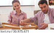 Купить «couple eating takeaway pizza at home», видеоролик № 30975671, снято 10 июня 2019 г. (c) Syda Productions / Фотобанк Лори